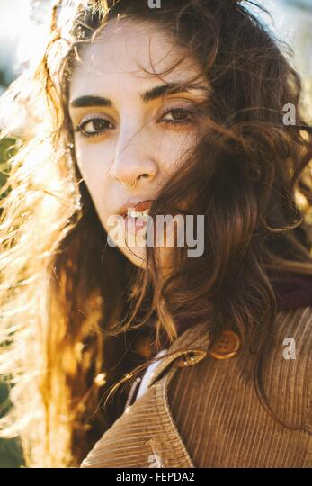 Portrait of young woman with wavy hair, close-up - Stock Image