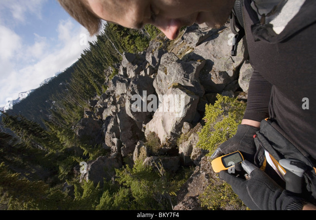 A man checks his location on a GPS (global positioning system) near Squamish, British Columbia. - Stock Image