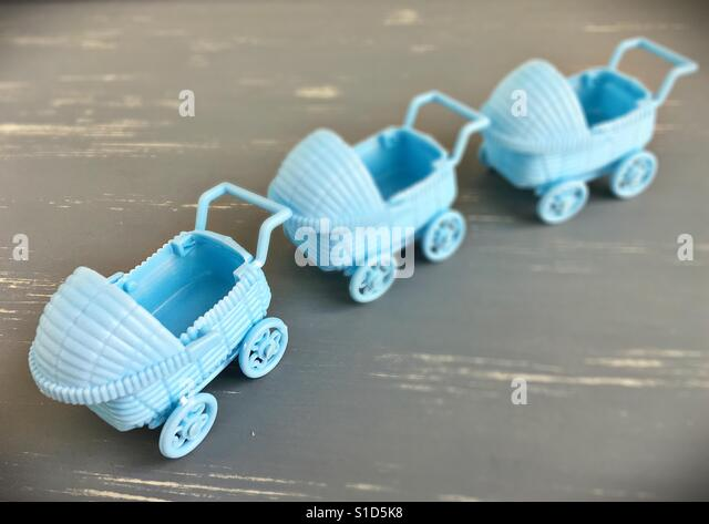 Three blue toy baby carriages in a line. - Stock Image