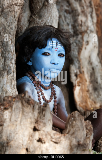 Indian boy, face painted as the Hindu god Shiva sitting in an old tree stump. Andhra Pradesh, India - Stock Image