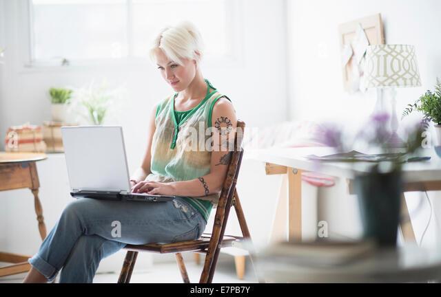 Woman using laptop at home - Stock-Bilder