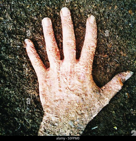 Double exposure of a hand and garden compost - Stock Image