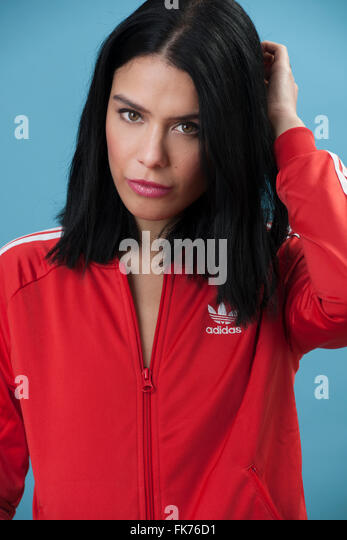 Female model wearing a red retro Adidas zip jacket - Stock Image