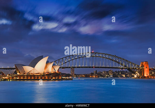 Sydney, Australia, 18 March 2017: World famous Sydney Opera House and Harbour bridge at sunset. Blurred clouds and - Stock Image