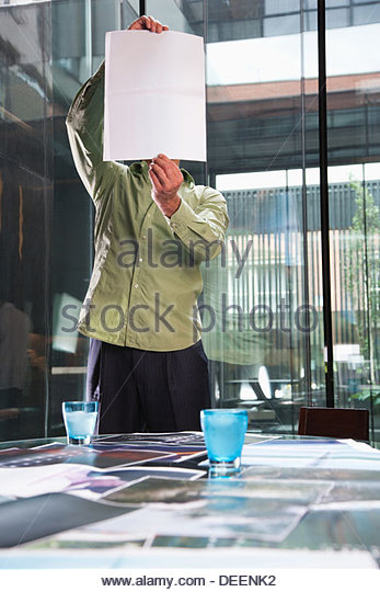 Businessman looking at a piece of paper in an office - Stock Image