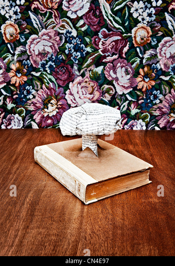 Nuclear cloud made out of printed paper coming out of book - Stock Image