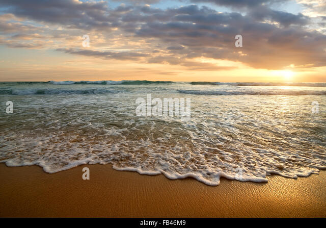 Bright cloudy sunset in the calm ocean - Stock Image