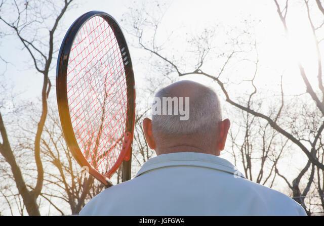 Rear view of Hispanic man holding tennis racket - Stock Image