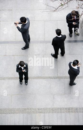 Businessmen using cellphones - Stock Image