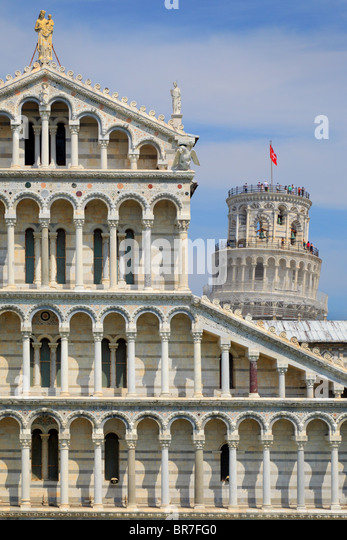 The Duomo with the iconic Leaning Tower behind it, in Pisa's Square of MIracles, Italy - Stock Image