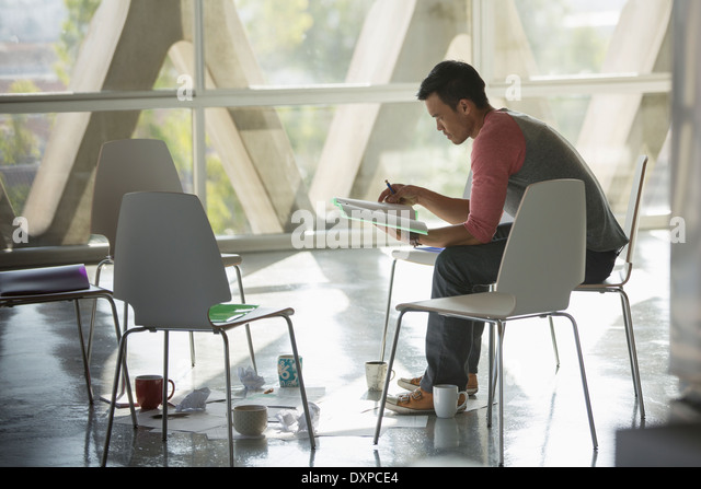 Businessman reviewing paperwork at circle of chairs - Stock Image