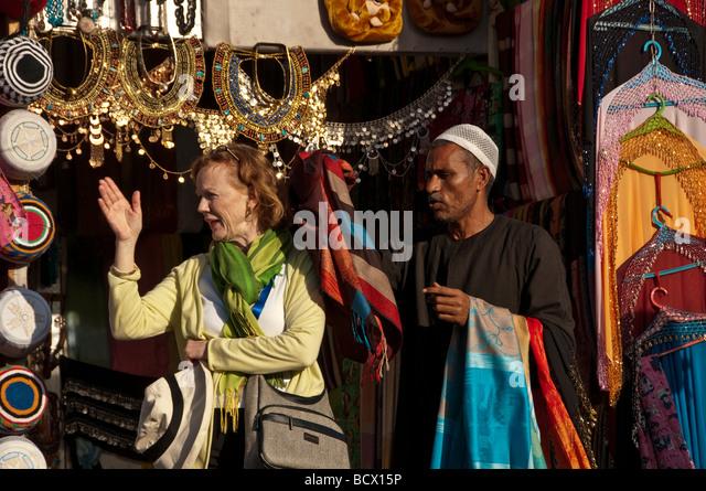 Egypt Kom Ombo woman tourist waves away persistent souvenir seller - Stock Image