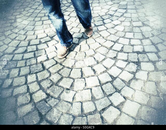 Man walking on cobbled road - Stock Image