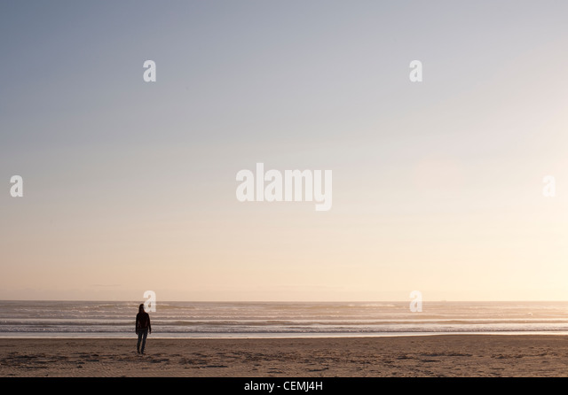 Woman walking along ocean beach alone in tranquil scene - Stock Image