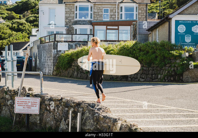 A surfer walking his board, Sennen Cove, Cornwall - Stock Image
