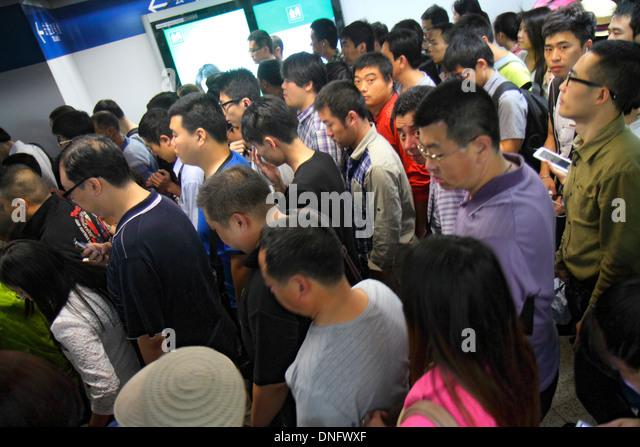 Beijing China Xuanwumen Subway Station public transportation Line 4 passenger rider Asian man woman platform crowded - Stock Image