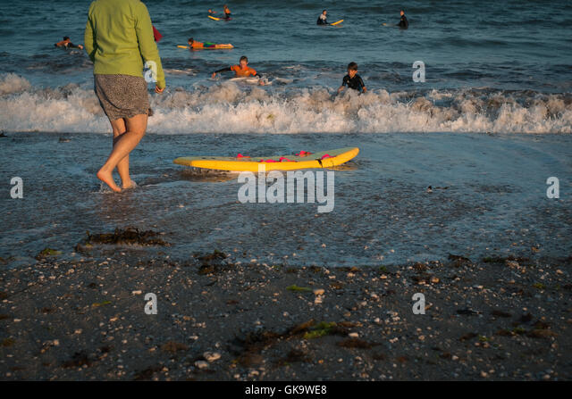 A mum stands by the shoreline watching her son enjoying the late evening surf at Gyllyngvase Beach, Falmouth, Cornwall - Stock Image