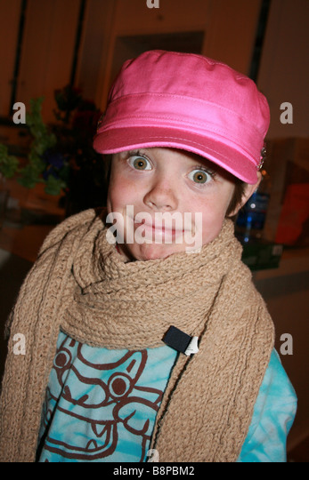 six year old boy dressed up as a girl wearing a pink hat and lipstick - Stock Image