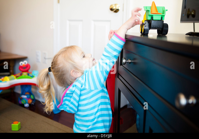 Girl Reaching for Toy - Stock Image