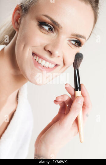 Woman applying makeup on face - Stock Image