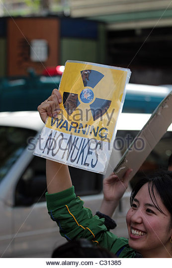 An activists holds up a sign reading 'warning no nukes' during a protest march in Shibuya, Tokyo. - Stock Image