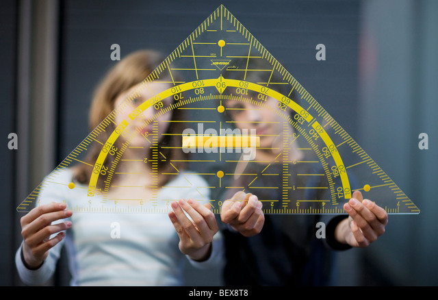 Students holding a big triangle - Stock-Bilder