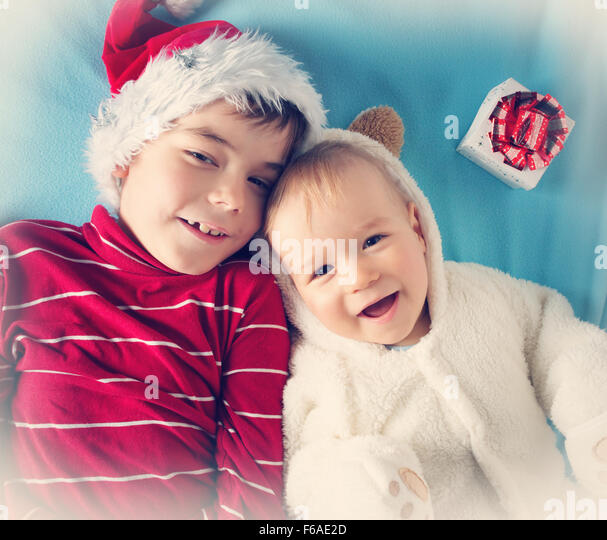 Two brothers, one and six years old in santa, bear costumes - Stock Image