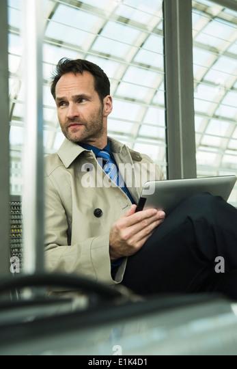 Businessman at train station using digital tablet - Stock Image