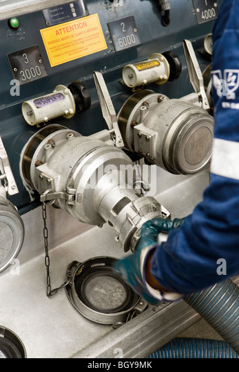 Connecting hoses to fuel tanker outlets - Stock Image