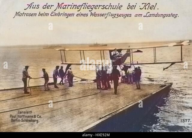 German World War I photographic postcard depicting sailors with a seaplane at the landing stage at a naval flying - Stock Image