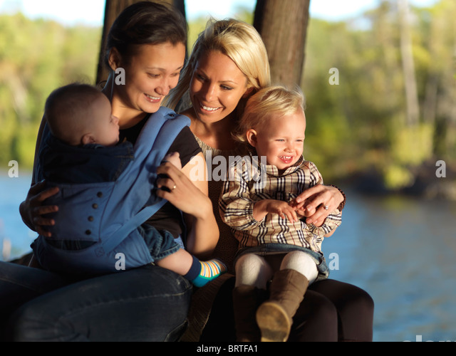 Two young mothers with their kids enjoying their time in the nature. Ontario, Canada. - Stock Image