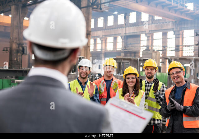 Steel workers clapping for manager in meeting in factory - Stock Image