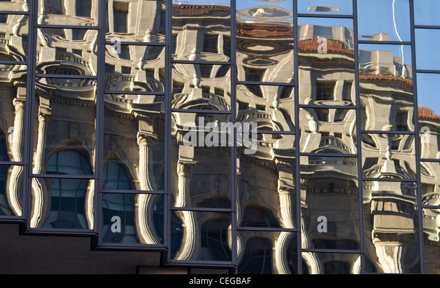 Distorted reflections of a building in neoclassical style reflected in the windows of a modern glass high-rise block. - Stock Image