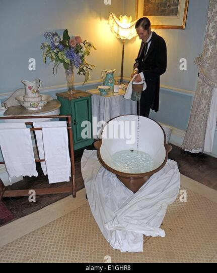 Victorian bath with butler pouring hot water in a tiled en-suite bathroom. - Stock Image