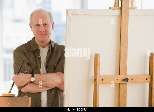 Senior man standing next to easel - Stock Image