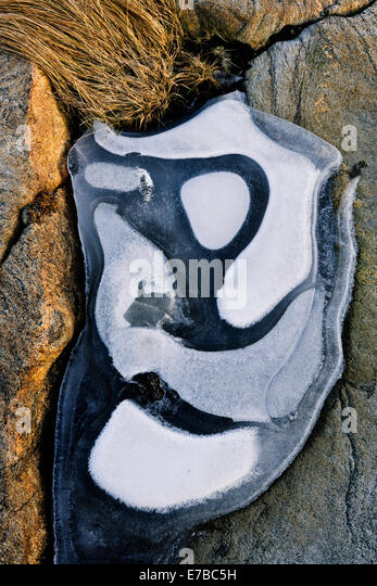 Pattern of white frost on a black boulder - Stock Image
