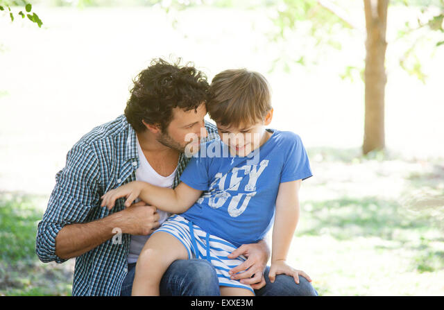 Boy sitting on father's lap - Stock Image