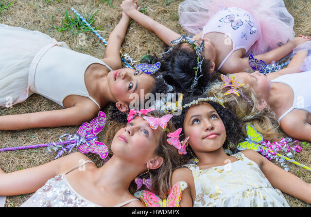 Group of young girls dressed as fairies, lying in circle, heads together - Stock-Bilder