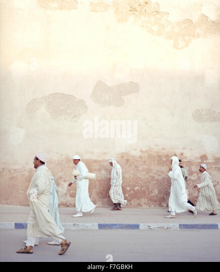 Moroccan Muslim men walk briskly past the city walls on their way to morning prayers. Essaouira, Morocco,North Africa. - Stock Image