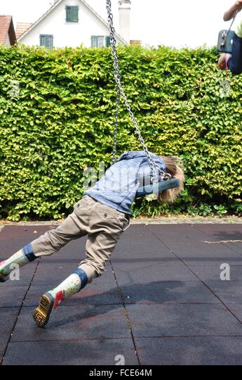 Side View Of A Boy On Swing At Playground - Stock Image