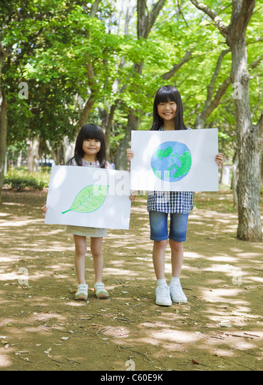 Sisters holding drawings of leaf and globe - Stock-Bilder