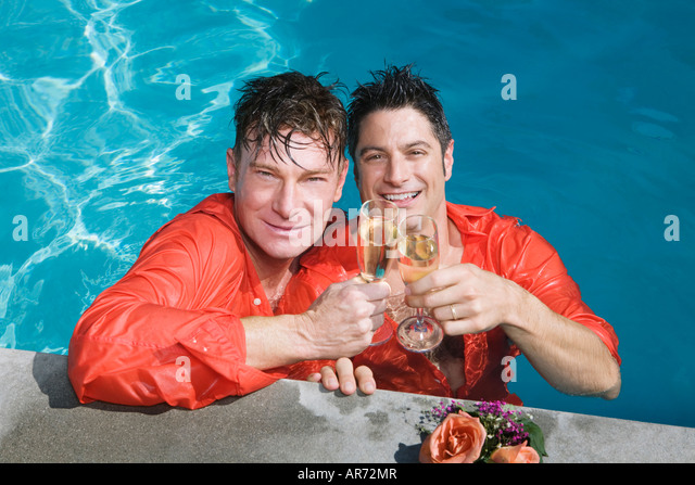 Fully clothed gay couple drinking champagne in swimming pool - Stock-Bilder