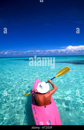 man kayaking in tropics green water blue sky escape remote ideal paradise perfect sports outdoor recreation cruise - Stock Image