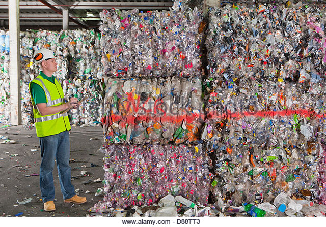 Worker examining bales of recycled plastic in recycling plant - Stock Image
