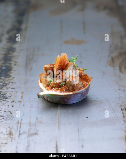 Bite-size fig with pork - Stock Image