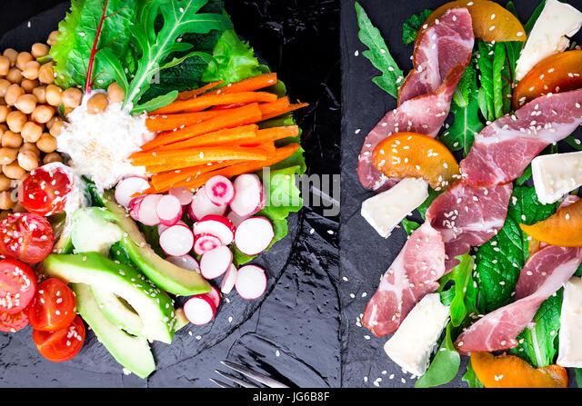 Two different salads om black stone slate. Vegan salad. Meat salad. Salad with ham jamon serrano, camembert, melon, - Stock Image