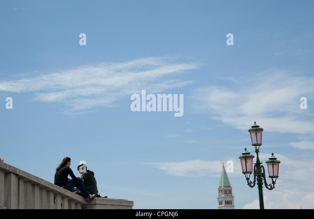 A young couple sit on a bridge overpass near St. Marks Square in Venice, Italy. - Stock Image