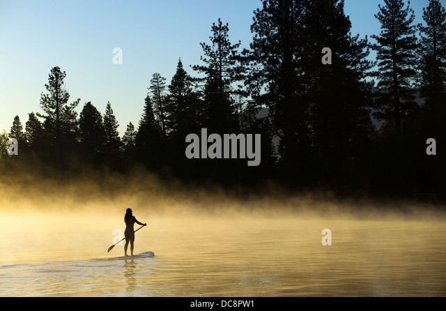 A woman, , is silhouetted Stand Up Paddleboarding (SUP) at sunrise in the mist in Lake Tahoe, CA. - Stock-Bilder