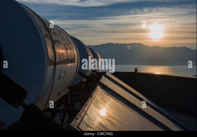 An array of solar water heaters (tanks and collector panels) on roof of an apartment building, Israel - Stock Image