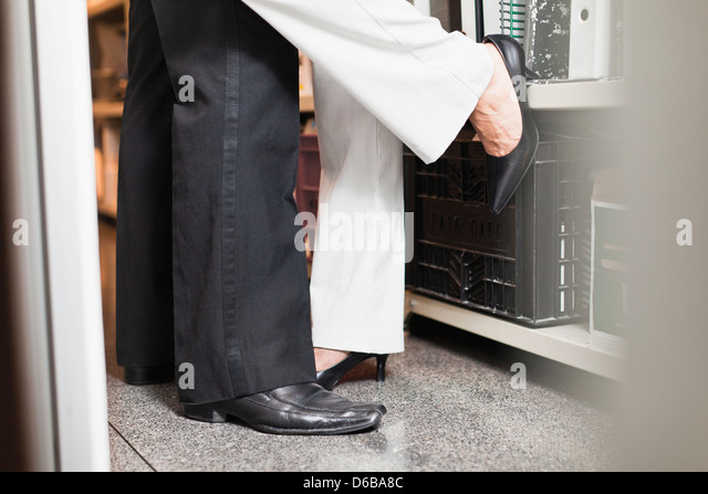 Business people kissing in closet - Stock-Bilder